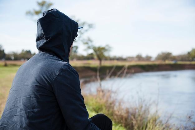 Homem, relaxante, por, a, lado lago, vista
