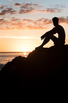 Homem, relaxante, praia, em, pôr do sol