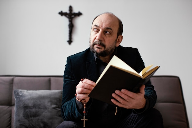 Homem religioso lendo um livro sagrado em casa