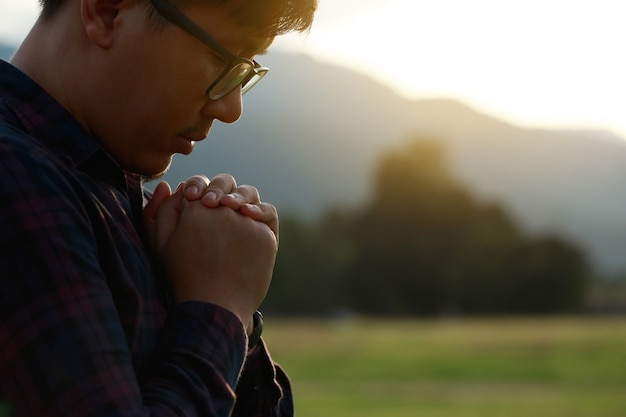 Homem religioso orando a deus com o queixo sobre as mãos em um campo durante um lindo pôr do sol