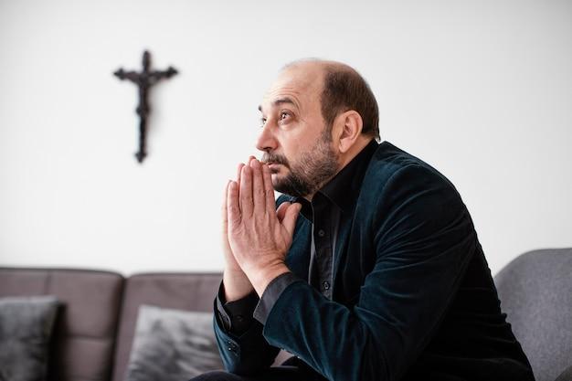 Homem religioso rezando em casa