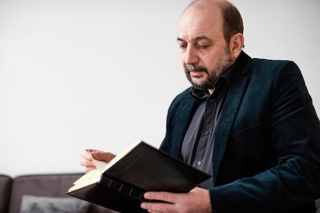 Homem religioso segurando um livro sagrado dentro de casa