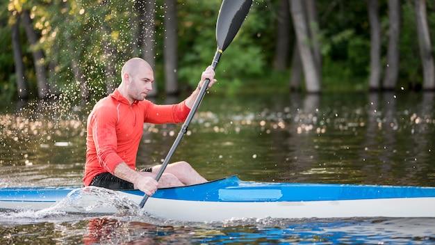 Homem remando em canoa azul vista lateral