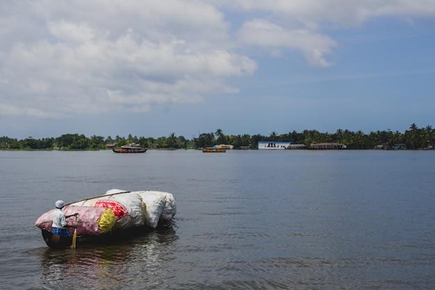 Homem remando uma canoa de madeira cheia de plástico