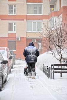 Homem remove a neve no quintal de um edifício de vários andares com máquinas de neve