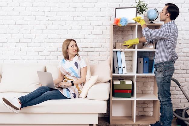 Homem remove a poeira da prateleira e mulher no apartamento