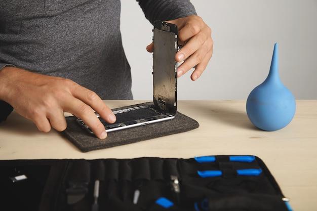 Homem remove tela quebrada em seu smartphone para trocá-la, serviço de conserto eletrônico