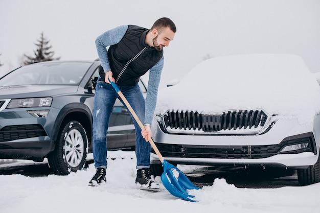 Homem removendo neve com uma pá perto do carro