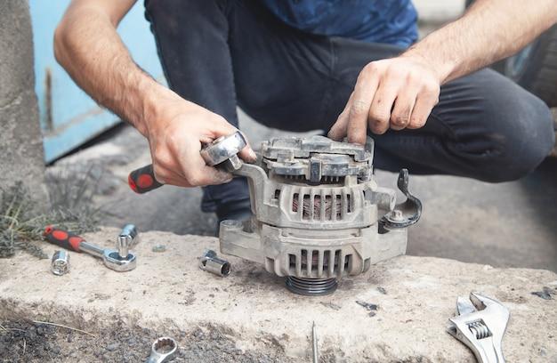 Homem repara o alternador do carro. centro de serviço