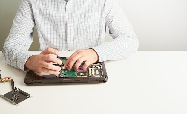 Homem repara o computador. um engenheiro de serviço em camisa repara o laptop, na mesa branca contra a parede branca.