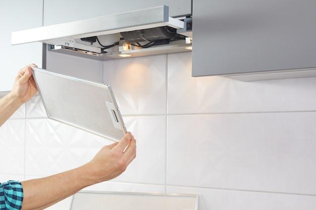 Homem repara o exaustor na cozinha. filtro de reposição em um exaustor.