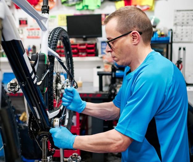 Homem repara uma bicicleta em sua oficina de pequenas empresas