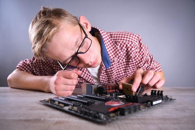 Homem reparando computador quebrado, placa de vídeo, memória ram, refrigerador, processador, disco rígido. jovem reparador trabalhando com chave de fenda no centro de serviço.