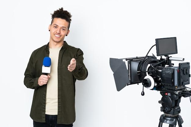 Homem repórter segurando um microfone e relatando notícias sobre aperto de mão após um bom negócio