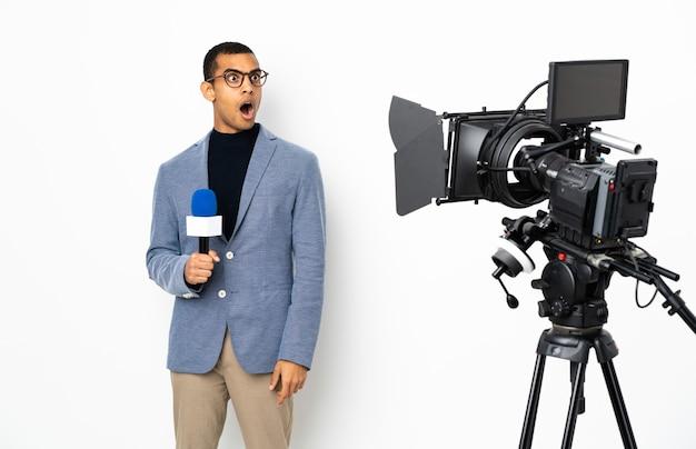 Homem repórter segurando um microfone e relatando notícias sobre uma parede branca isolada fazendo gesto de surpresa enquanto olha para o lado