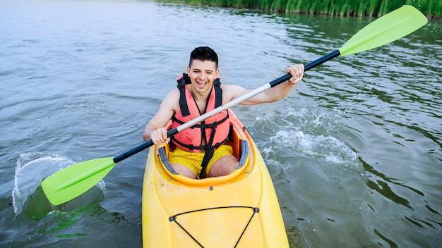 Homem, respingue água, com, remo, enquanto, kayaking, ligado, lago