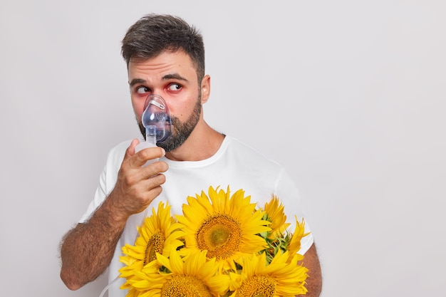 Homem respira através de máscara de oxigênio tem alergia a girassóis olhos lacrimejantes vermelhos desvia o olhar sofre de febre do feno poses em branco