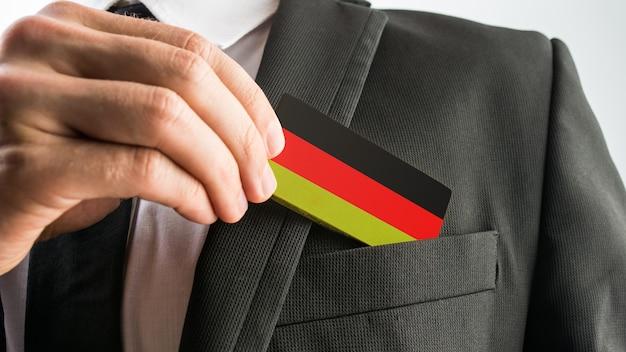 Homem retirando do bolso do paletó um cartão de madeira pintado como a bandeira alemã.