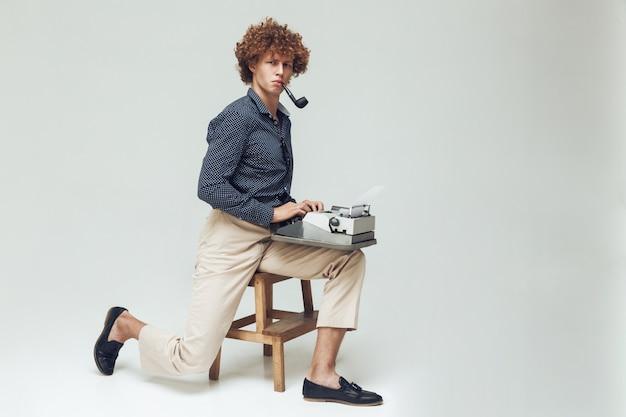 Homem retrô sério com cachimbo segurando a máquina de escrever.