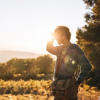 Homem retroiluminado usando binóculos