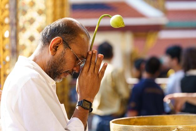Homem rezando ao lado de uma fonte
