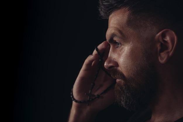 Homem rezando com rosário ou contas de oração, reze, pense no futuro retrato emocional bonito barbudo