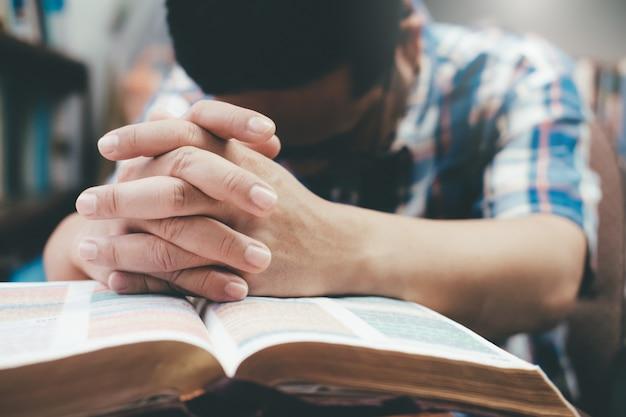 Homem rezando, mãos entrelaçadas em sua bíblia.