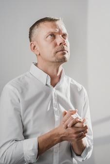 Homem rezando para a divindade em casa