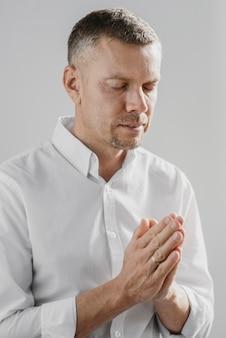 Homem rezando sozinho dentro de casa