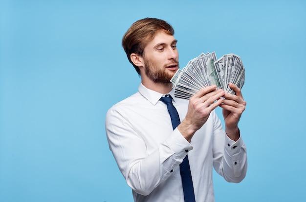 Homem rico de terno com dinheiro nas mãos, emoções, parede azul