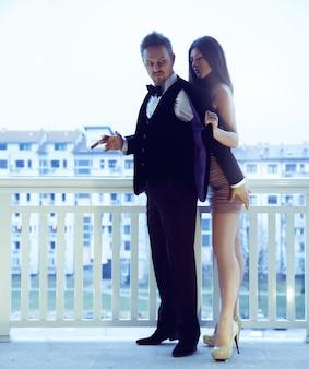 Homem rico e bonito fumando um charuto e tocando sua bunda de mulher e flertando com ela. o conceito de paixão, amor e relacionamentos