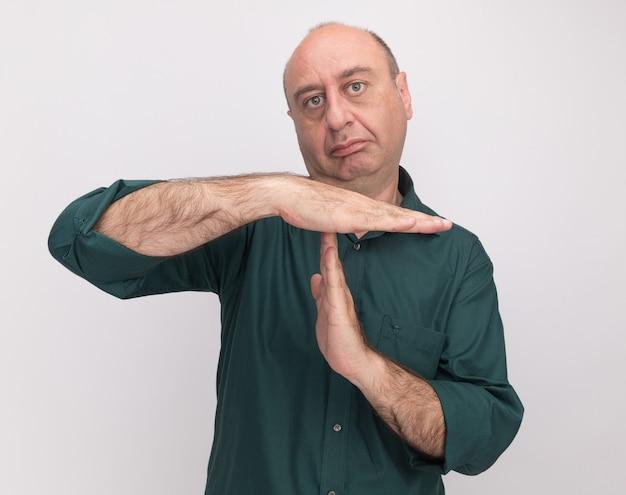 Homem rígido de meia-idade vestindo camiseta verde e mostrando gesto de tempo limite isolado na parede branca