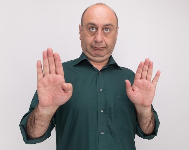 Homem rígido de meia-idade vestindo uma camiseta verde e mostrando um gesto de pare isolado na parede branca