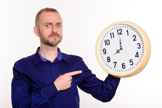 Homem rígido segurando um grande relógio de parede e apontando o dedo para eles em branco