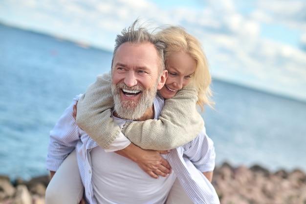 Homem rindo carregando mulher nas costas
