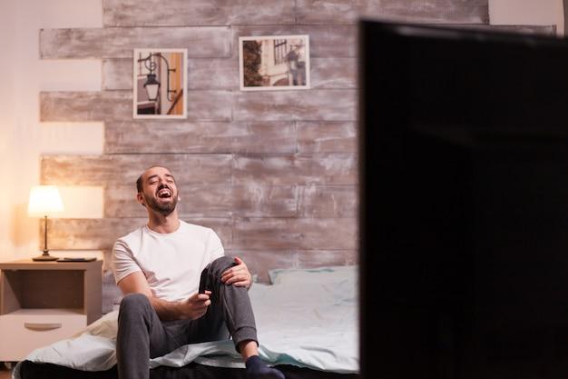 Homem rindo na cama à noite, assistindo a um reality show.