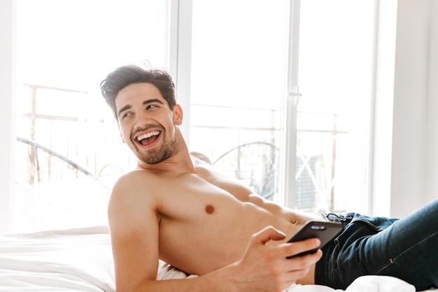 Homem rindo sem camisa segurando um celular