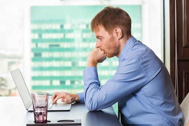 Homem roendo as unhas enquanto olha para um laptop