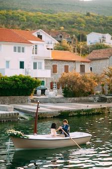 Homem rola uma mulher em um barco decorado com flores no contexto do cais e casas antigas