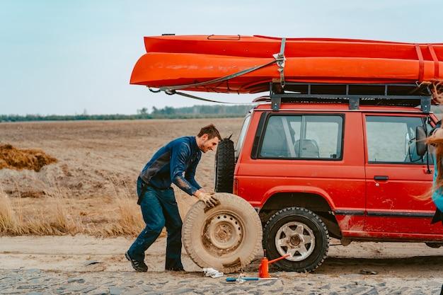 Homem rola uma nova roda de substituição para caminhão 4x4 fora de estrada