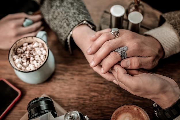 Homem romanticamente segurando as mãos de uma mulher em uma mesa de café