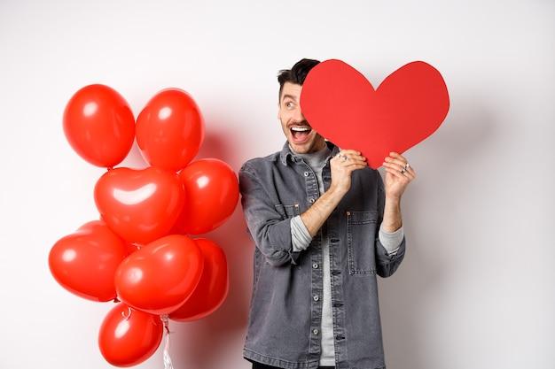 Homem romântico alegre cobrir metade do rosto com recorte de coração dos namorados e sorrindo espantado, comemorando o feriado de amor, em branco.