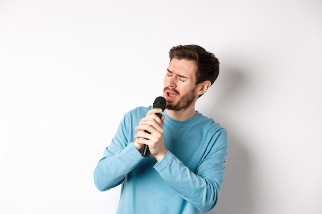 Homem romântico cantando uma música no microfone no karaokê, em pé sobre um fundo branco.