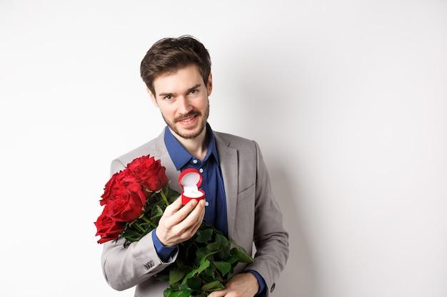 Homem romântico com boquet de rosas vermelhas, pedindo em casamento, segurando o anel de noivado e olhando confiante para a câmera, em pé de terno sobre fundo branco.