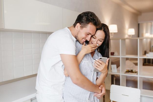 Homem romântico com penteado curto abraçando uma senhora morena sorridente usando um pijama fofo