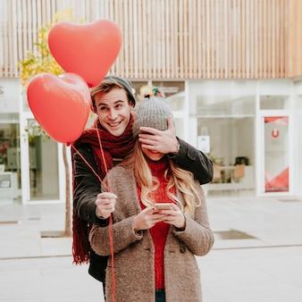 Homem romântico mulher surpreendente com balões