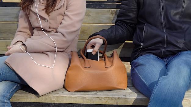 Homem rouba o telefone da bolsa de uma mulher no parque.