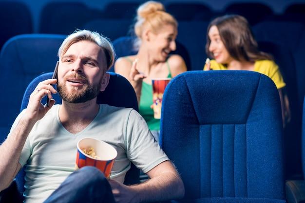 Homem rude falando ao telefone e incomodando mulheres nos assentos de trás do cinema