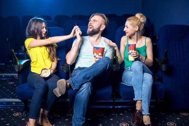 Homem rude falando ao telefone sentado com mulheres no cinema