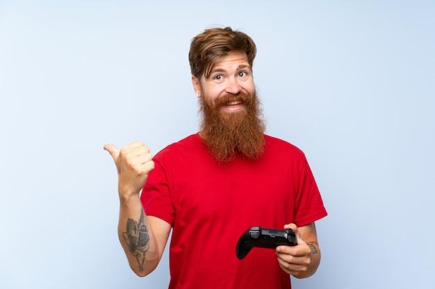 Homem ruiva com barba longa, jogando com um controlador de vídeo game apontando para o lado para apresentar um produto